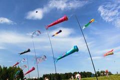 Os papagaios Multicoloured voam no céu ventoso azul imagens de stock