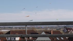 Os papagaios sobem sobre os telhados das casas a vista do balcão vídeos de arquivo