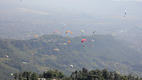 Os Paragliders em paraquedas coloridos voam sobre a cidade em um vale verde da montanha filme