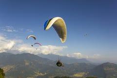 Os Paragliders voam sobre um vale verde da montanha contra um céu azul e umas nuvens brancas fotografia de stock