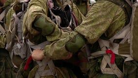 Os paramilitares militares dos soldados verificam paraquedas e equipamento antes de saltar vídeos de arquivo