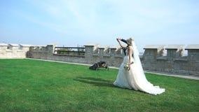 Os pares à moda de recém-casados no amante estão guardando as mãos e estão dançando ao andar ao longo do jardim de florescência p filme