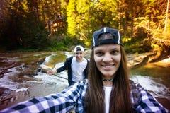 Os pares à moda tomam o selfie na câmera perto do rio rápido na floresta fotografia de stock