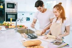 Os pares adolescentes asiáticos estão ajudando a fazer o jantar Fotos de Stock Royalty Free