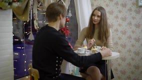Os pares agradáveis de jovens no café falam Menina que sorri em seu noivo, bebe o café, mãos mornas Bonito filme