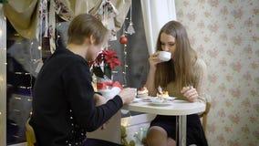 Os pares agradáveis de jovens no café falam Menina que sorri em seu noivo, bebe o café, mãos mornas Bonito vídeos de arquivo