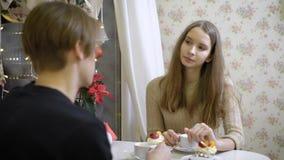 Os pares agradáveis de jovens no café falam Menina que sorri em seu noivo, bebe o café, mãos mornas Bonito video estoque