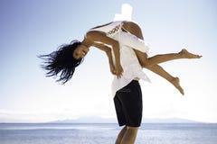 Os pares alegres jogam na praia, homem que guarda uma amiga em seus ombros, em um céu claro, nas horas de verão imagens de stock