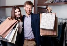Os pares alegres mostram suas compras Foto de Stock Royalty Free