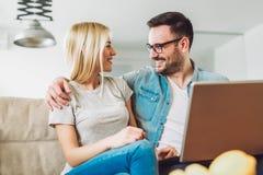 Os pares alegres relaxam e trabalham no laptop na sala de visitas moderna imagem de stock royalty free