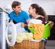 Os pares aproximam a máquina de lavar em casa imagem de stock