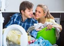 Os pares aproximam a máquina de lavar em casa fotos de stock