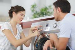 Os pares aproximam a m?quina de lavar em casa imagem de stock