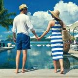Os pares aproximam a piscina foto de stock