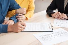 Os pares asiáticos assinam o contrato home com corretor de imóveis em casa compra nova imagens de stock royalty free