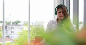 Os pares asiáticos discutem sobre seu negócio Mulher asiática posta sobre o fones de ouvido filme