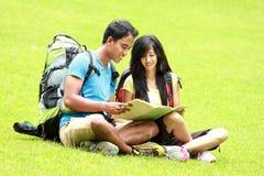 Os pares asiáticos novos leram um mapa e o assento na grama Foto de Stock Royalty Free