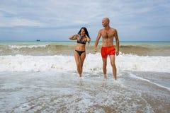 Os pares atrativos no mar no verão nublam o dia fotos de stock royalty free
