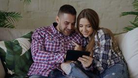 Os pares atrativos novos usando o tablet pc para o Internet surfando e conversando sentam-se no sofá na sala de visitas em casa filme
