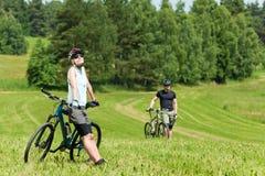 Os pares biking da montanha do esporte relaxam nos prados Fotos de Stock