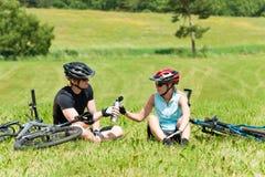Os pares biking da montanha do esporte relaxam prados ensolarados Foto de Stock
