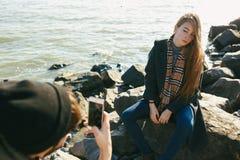 Os pares bonitos e à moda são fotografados em uma praia rochosa Os pares vestiram-se nos revestimentos, nos chapéus e nas botas Fotografia de Stock Royalty Free