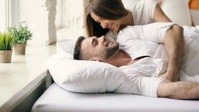 Os pares bonitos e loving novos acordam na manhã O beijo atrativo da mulher e abraça seu marido na cama fotografia de stock royalty free