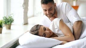 Os pares bonitos e loving novos acordam na manhã O beijo atrativo do homem e abraça sua esposa na cama imagens de stock