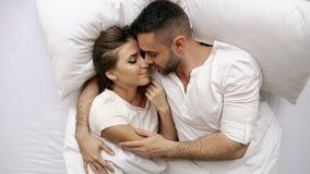 Os pares bonitos e loving novos beijam e abraçam na cama ao acordar na manhã Opinião superior o homem atrativo fotografia de stock royalty free