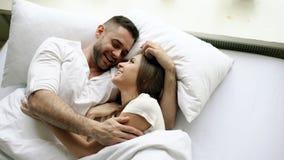 Os pares bonitos e loving novos falam e abraçam na cama ao acordar na manhã Opinião superior o homem atrativo fotografia de stock