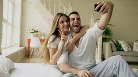 Os pares bonitos e loving novos tomam a imagem do selfie na câmera do smartphone ao sentar-se na cama na manhã imagem de stock royalty free
