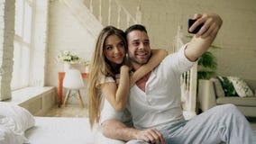 Os pares bonitos e loving novos tomam a imagem do selfie na câmera do smartphone ao sentar-se na cama na manhã fotografia de stock royalty free