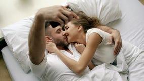 Os pares bonitos e loving novos tomam a imagem do selfie na câmera do smartphone e beijam-na ao encontrar-se na cama na manhã imagem de stock