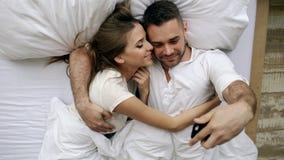 Os pares bonitos e loving novos tomam a imagem do selfie na câmera do smartphone que encontra-se na cama na manhã imagens de stock