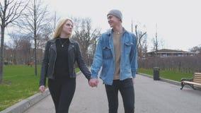 Os pares bonitos, louros novos e seu noivo estão andando no parque, guardando as mãos Vá à câmera Um bonito filme