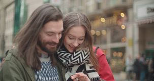 Os pares bonitos novos compartilham de memórias e de imagens em meios sociais com o móbil em linha app filme