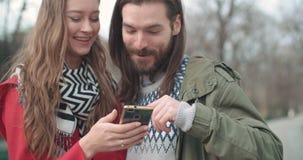 Os pares bonitos novos compartilham de memórias e de imagens em meios sociais com o móbil em linha app video estoque
