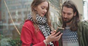 Os pares bonitos novos compartilham de memórias e de imagens em meios sociais com o móbil em linha app vídeos de arquivo