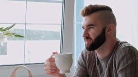 Os pares bonitos novos em camisetas mornas em uma casa de campo est?o sentando-se na tabela branca na perspectiva do vídeos de arquivo