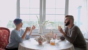 Os pares bonitos novos em camisetas mornas em uma casa de campo est?o sentando-se na tabela branca na perspectiva do video estoque