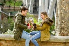 Os pares bonitos novos no amor que comemora presentes do dia de Valentim e aumentaram Imagem de Stock
