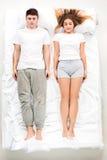 Os pares bonitos novos que encontram-se em uma cama Imagens de Stock