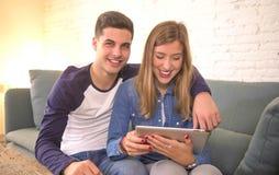 Os pares bonitos novos 20s que usam a tabuleta digital acolchoam o computador que senta em casa a compra da sala de visitas do so Imagens de Stock Royalty Free