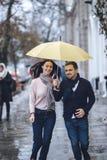 Os pares bonitos, o indivíduo e sua amiga vestidos na roupa ocasional estão correndo sob o guarda-chuva na rua no imagem de stock royalty free