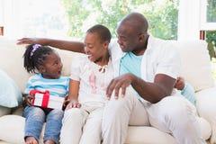 Os pares bonitos oferecem um presente para sua filha Imagens de Stock Royalty Free