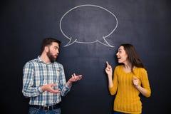 Os pares bonitos que falam sobre o fundo do quadro-negro com discurso borbulham Fotografia de Stock