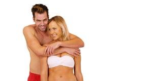 Os pares brancos novos alegres que estão na frente da praia vestindo do fundo branco attire imagens de stock royalty free
