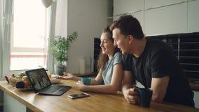 Os pares caucasianos alegres novos que sentam-se na tabela na frente do portátil que skyping com seu positivo feliz bronzearam-se video estoque