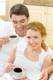Os pares com café bebem em casa fotografia de stock