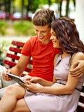 Os pares com PC da tabuleta sentam-se no banco Imagens de Stock Royalty Free